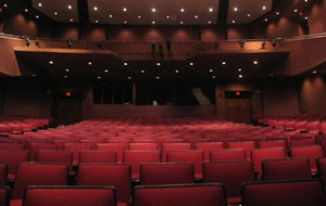 A house full of scarlet colored empty seats seen from the stage